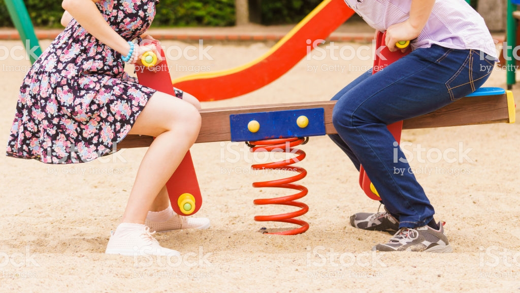 couple having fun on playground for kids. teenagers being on funny date.